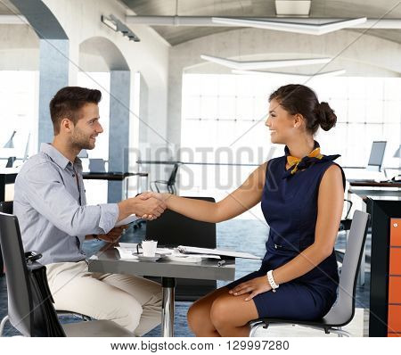 Young businesspeople sitting at coffee table, smiling, shaking hands. Side view.