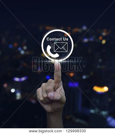 Hand pressing telephone and mail icon button over blurred light city tower background Contact us concept