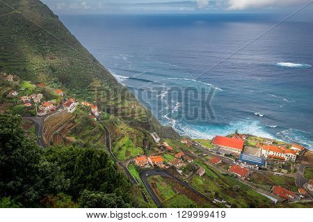Aerial view of steep serpentine road from the mountains down to Porto Moniz town on the shore of Atlantic ocean. Madeira island, Portugal.