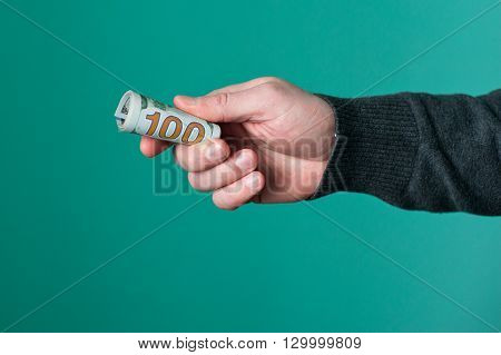 Human hand holding rolled up paper dollar currency.