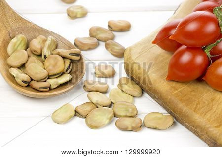 Dried broad beans and fresh tomatoes on wooden background