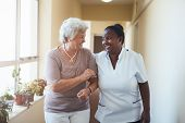 Smiling Home Caregiver And Senior Woman Walking Together poster