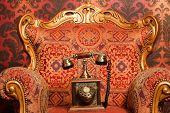 Постер, плакат: Старый телефон является красный стул с золотой акцентами красный винтажные обои Фокус на телефоне