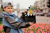 A boy in jacket and cap with cinema clapper board in hands standing on field with tulips on of urban