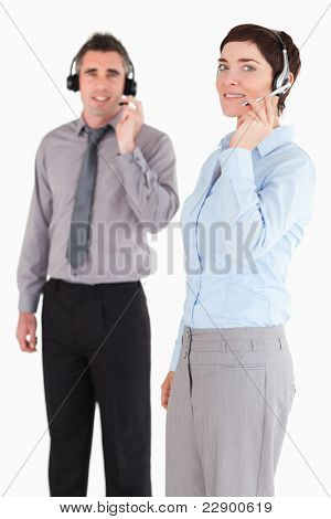 Portrait of managers speaking through headsets against a white background