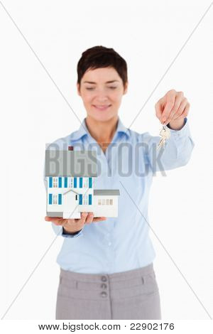 Real estate agent showing keys and a miniature house against a white background
