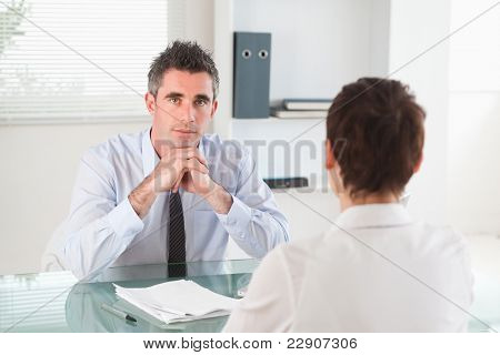 Serious manager interviewing a female applicant in his office