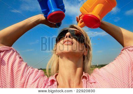 Hermosa mujer riego a sí misma en un caluroso día de verano