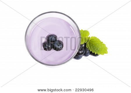 blueberries on top of a blueberry milkshake with blueberries and melissa aside