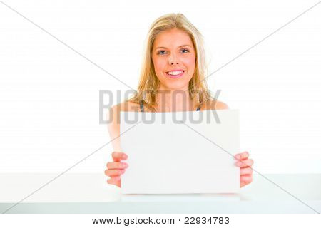 Lovely Girl Sitting At Table And Holding Blank Paper