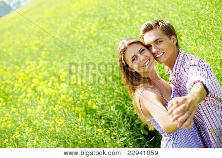 Retrato de la feliz pareja joven de manos en el campo de la flor