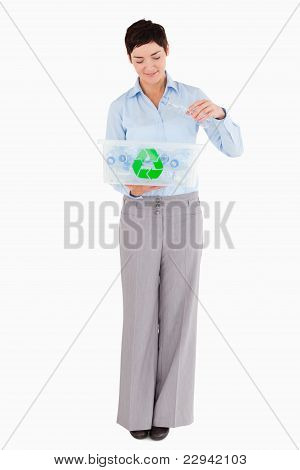 Woman Putting An Empty Plastic Bottle In A Recycling Box