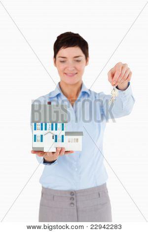 Immobilienmakler mit Schlüssel und ein Miniatur-Haus