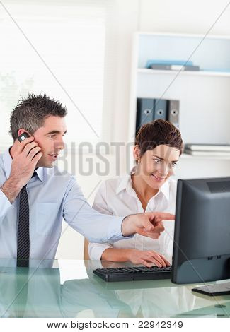 Portrait Of A Man Showing Something To His Coworker On A Compute