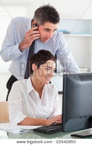 Man Making A Phone While Looking At His Colleague's Screen