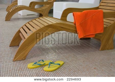 Sunbed With Towel  And Yellow Sandals Near From Left