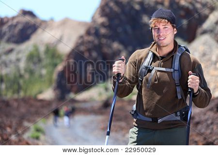 Adventure hiking man. Portrait in mountain landscape. Caucasian male hiker smiling in nature standing with hiking poles in volcano landscape on Teide, Tenerife, Canary Islands