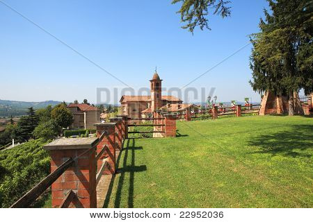 View on old church from green lawn surrounded by brick fence in Grinzane Cavour - small town in northern Italy.