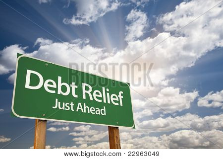 Debt Relief, Just Ahead Green Road Sign Over Dramatic Sky, Clouds and Sunburst.