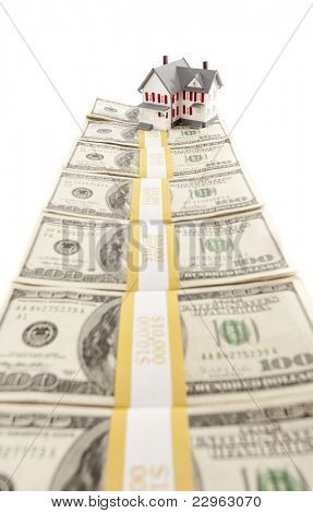 Small House on Row of Hundred Dollar Bill Stacks Isolated on a White Background.