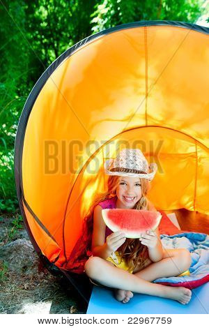 children girl in camping tent eating watermelon slice at forest