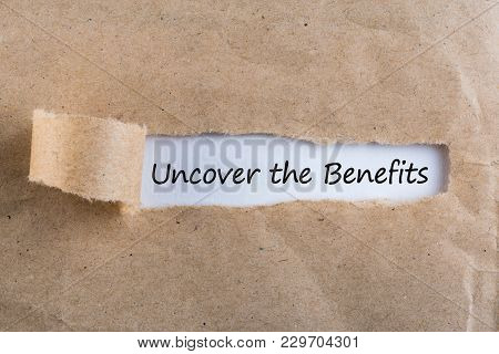 poster of Uncover The Benefits Text On Brown Envelope. Word Uncover The Benefits On Torn Paper. Concept Image.