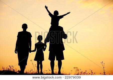 Silhouette, happy children with mother and father, family at sunset, summertime