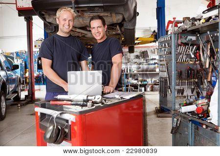 Portrait of mechanics with laptop in auto repair shop
