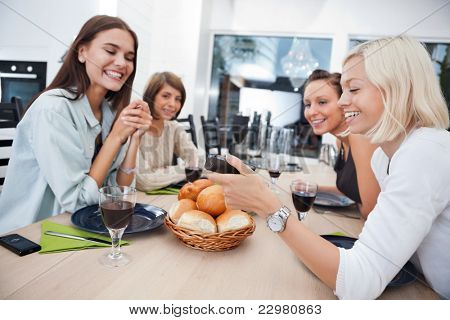 Women showing something to her friends on mobile phone at dining table - Shallow Depth of field critical focus on phone