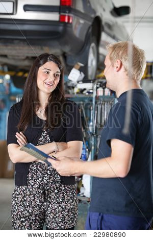 Smiling young woman and mechanic talking to each other in auto repair shop