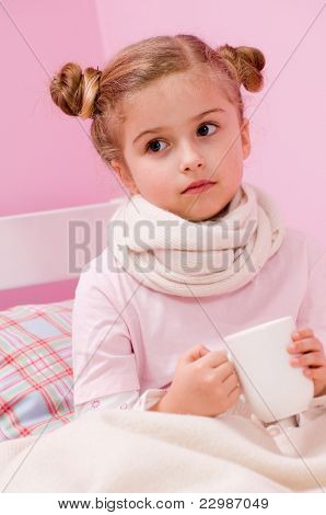 Cold and flu - sick girl with hot tea in bed