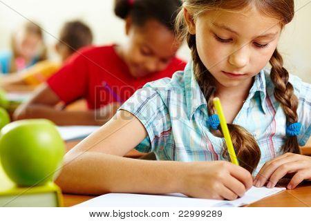 Retrato de niña preciosa dibujo en cuaderno en la lección