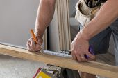 Close Up Male Constructor Carpenter Or Builder Hands Detail Working And Measuring Wood In Industrial poster