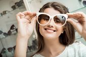 Pretty Brunette Girl Smiling, Trying On Sunglasses In Optical Shop. Charming Feminine Woman In Sungl poster
