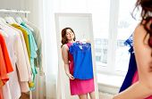clothing, fashion and people concept - happy plus size woman in pink dress with blue top looking at  poster