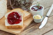 Delicious Toast Bread Served With Butter And Spread With Strawberry Jam. Sliced Bread On Wood Cuttin poster