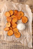 Parchment with tasty sweet potato chips on wooden table, top view poster