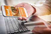 Ordering food online. Smartphone in hand and credit card in other. Concept of ordering food in offic poster