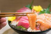 Chopsticks With Salmon Sashimi With Mixed Sliced Fish Sashimi On Ice In Black Bowl. Sashimi Salmon T poster