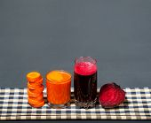 Natural Juices From Carrots And Beets. The Juice Is Poured Into A Clear Glass, Which Stands On A Tab poster