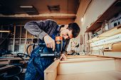 Man Builds Furniture In The Carpentry Shop. Toned Image. poster