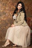 Beautiful Brunette Woman Wearing Beige Tulle Skirt On Golden Background. Brunette Hair Model poster