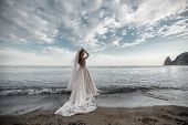 Beautiful Bride Stands On A Cliff Above The Sea In A Glamorous White Wedding Dress View Of Veil.roma poster