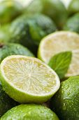 Backgrounds. Close Up Shot Of Wet Limes And Mint. Focus On The Central Part Of Sliced Lime. poster