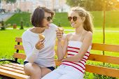 Holiday With The Family. Happy Young Mother And Cute Daughter Teenager In City Park Eating Ice Cream poster