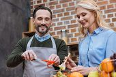 Happy Affectionate Couple Preparing Salad In Kitchen poster