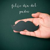 the text feliz dia del padre, happy fathers day in spanish, and the hand of a young caucasian man ho poster