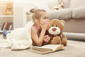 Cute Happy Little Casual Girl Embracing Teddy Bear, Reading Book And Sharing Secrets With Her Favori poster