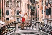 Romantic couple dancing jumping in love on Venitian canal bridge on honeymoon travel in Venice. Love poster