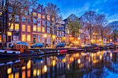 Night view of Amsterdam cityscape with canal, boats and medieval houses in the evening twilight illu poster
